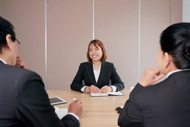 Уверенно азиатская коммерсантка сидя на встрече в офисе и усмехаться