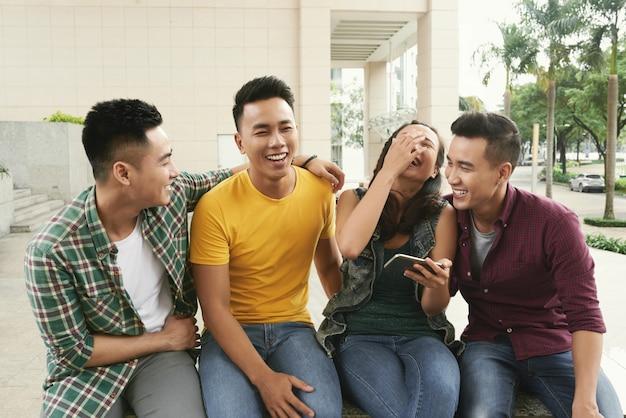 アジアの若い男性と都市通りで一緒に座って、笑っている女の子のグループ