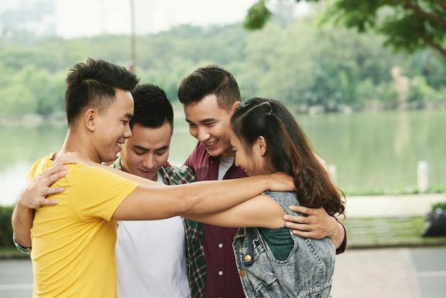 Четверо друзей-подростков обнимаются на улице у реки