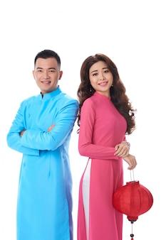 Довольно азиатские пары стоя плечом к плечу женщина держит китайский фонарь