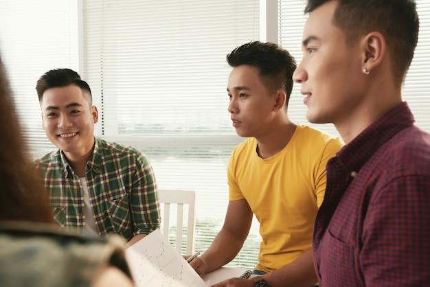Группа молодых небрежно одетых азиатских мужчин, сидящих и говорящих на встрече
