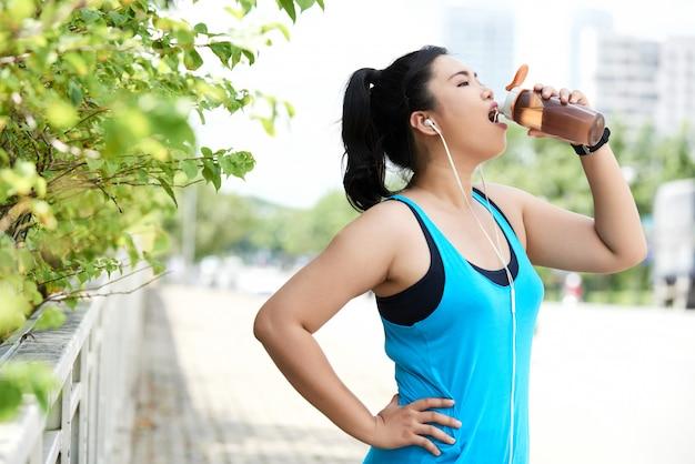 通りでスポーツボトルからエネルギーシェークを飲むアジアの女性のジョガー