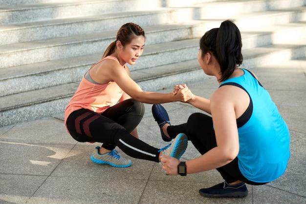 Две спортивные подруги делают приседания на одной ноге, держась за руки