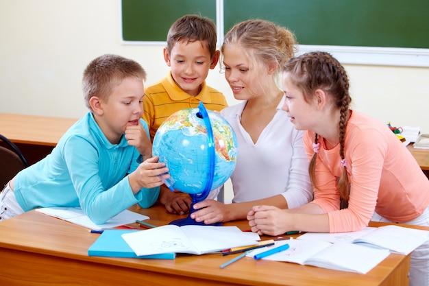 地球儀を見て地理の先生と生徒