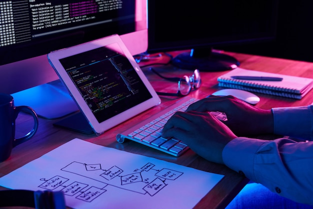 Крупным планом изображение программиста, работающего на своем столе в офисе