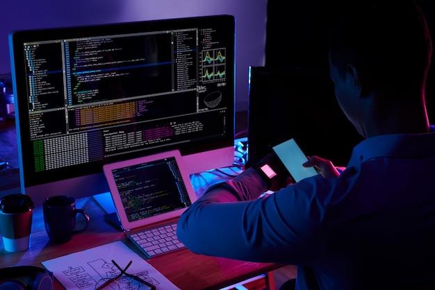 Программист сканирует экран на своих умных часах с камеры смартфона