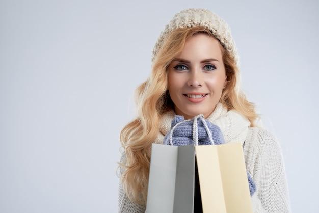 クリスマスセールで美しい女性の幸せな購入の中間のクローズアップ