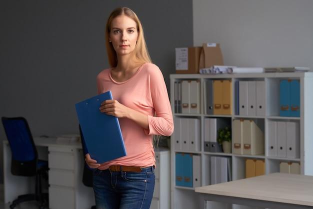Женский предприниматель позирует с папкой документов