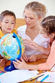 Учащиеся смотрят на глобус во время прослушивания учителя
