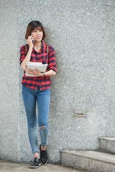 屋外のクラスの前に電話で話している女の子