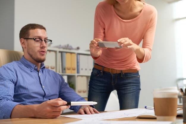 Два коллеги фотографируют распечатанный документ, над которым они работают