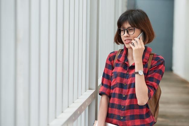 Молодой азиатский студент с рюкзаком имея телефонный звонок