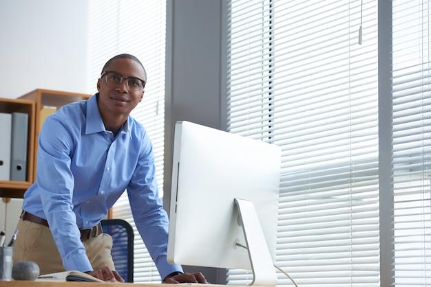 しんみりと見上げるオフィスに立っている彼のスタートアッププロジェクトに熱望している若い起業家