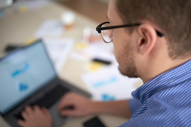 オフィスでコンピューティングしている男性の顔の肩越しのショット