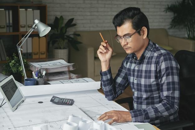 アジア人の彼の居心地の良いオフィスで青写真を描く