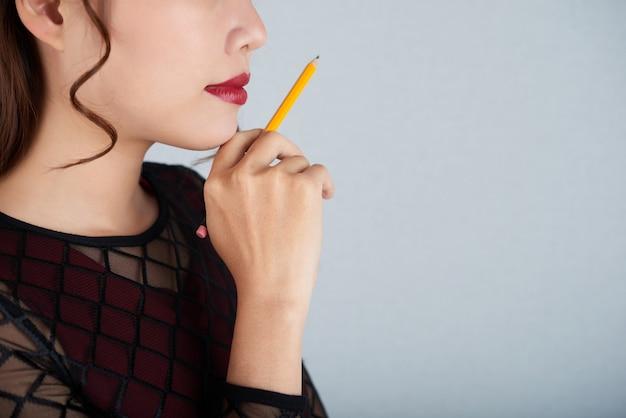 Обрезанное лицо женщины с жестом творческого мышления над бизнес-вызовом