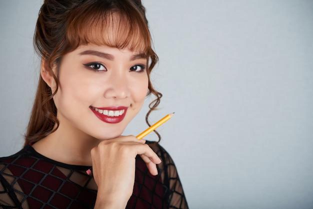 Красивая дама с рукой к подбородку держит ручку и улыбается