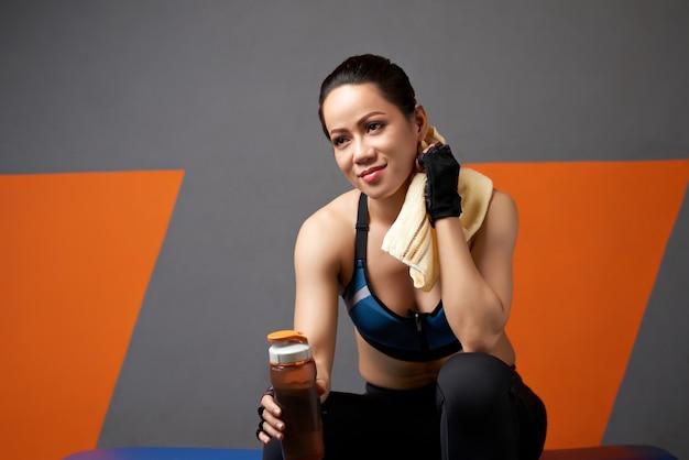 Среднего крупным планом спортивной девушки расслабиться после тренировки с бутылкой воды