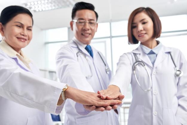 Поддерживающие медицинские коллеги складывают руки, чтобы показать сотрудничество - ключ к успеху