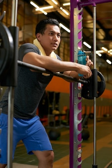 トレーニングから休憩を取る若い重量挙げ選手の側面図