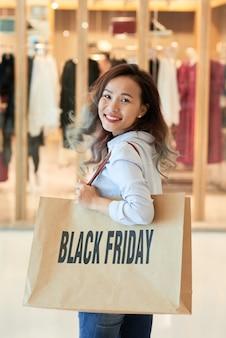 Молодая женщина, поворачиваясь, чтобы посмотреть на камеру в торговом центре