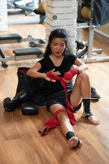 戦闘クラスの後、床に座っている女性のキックボクサー