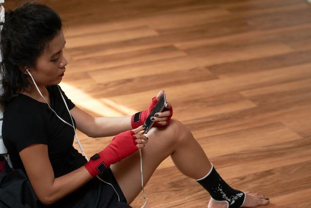 運動休憩で彼女のスマートフォンで音楽トラックを選択するスポーツウーマンのトップアングルビュー