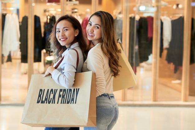 Вид сзади двух дам, делающих покупки в черную пятницу, оборачивающихся, чтобы смотреть на камеру