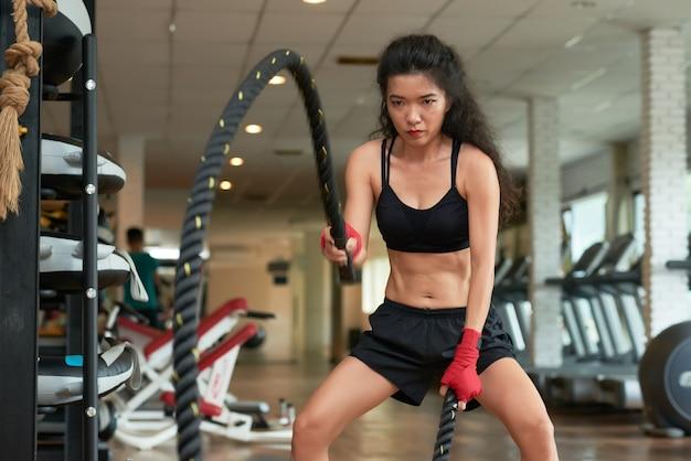 Средний снимок молодой спортсменки, делающей упражнение со скакалкой