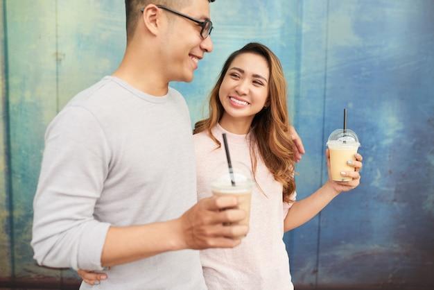 プロムナードの散歩にミルクセーキを持っているカップルのデートの側面図
