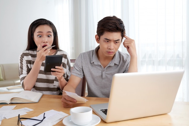 Молодая семья, делающая рутинный учет семьи, подчеркнула сумму расходов