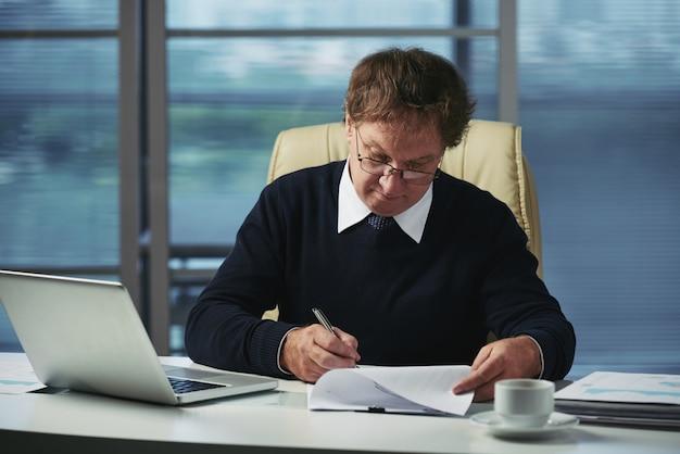 Топ-менеджер делает документы в своем офисе