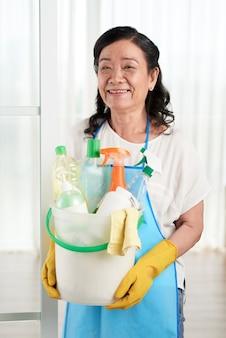 Домохозяйка держит ведро с моющими средствами