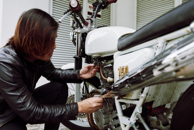 Вид сбоку мотоцикла, осматривающего его велосипед перед поездкой