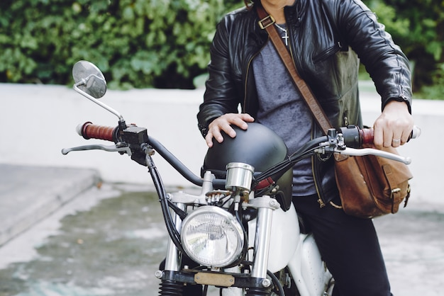 Средняя часть неузнаваемого человека в кожаной куртке с шлемом, сидящего на мотоцикле