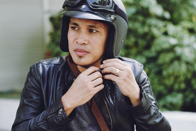 彼のヘルメットをかぶるバイカーのクローズアップ