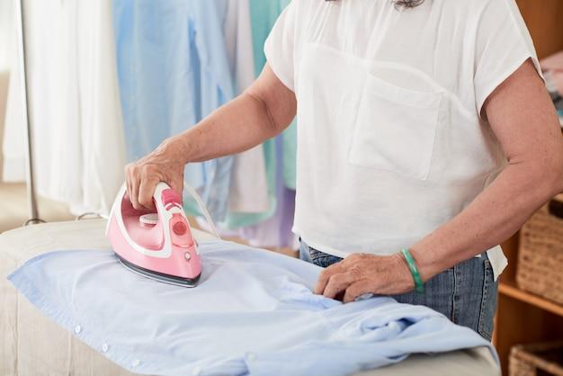 自宅で女性の中間セクションアイロンシャツの側面図