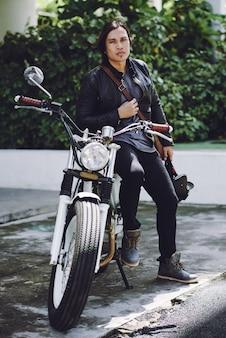 彼のバイクに傾いたバイカーの全身ビュー