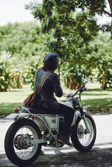晴れた日に自転車に乗って認識できない男の背面図