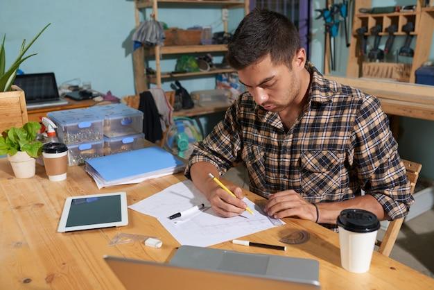 彼のワークショップで若いメーカー図面スケッチの角度のビュー