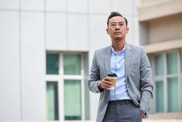 Средний снимок бизнесмена, держа кофе на вынос и с нетерпением жду, стоя на улице