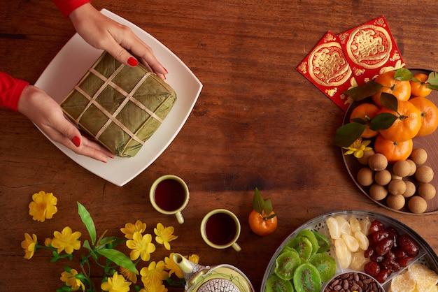 Вид сверху женских рук, где подают рисовый пирог