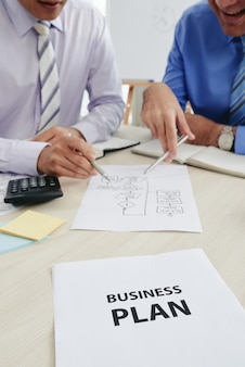 Обрезанные люди в торжественной одежде обсуждают бизнес-план