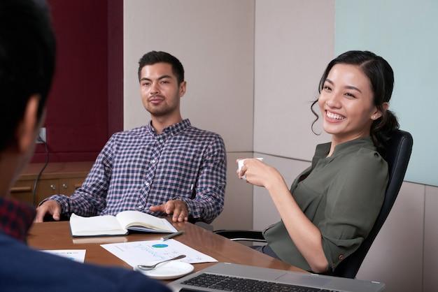 会議でコーヒーを飲んでいる陽気なビジネス女性の肖像画