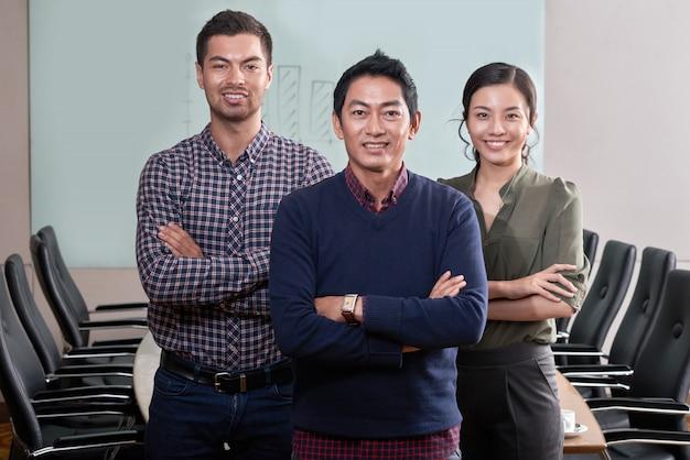 Уверенно бизнес команда стоя руки сложенными в конференц-зале
