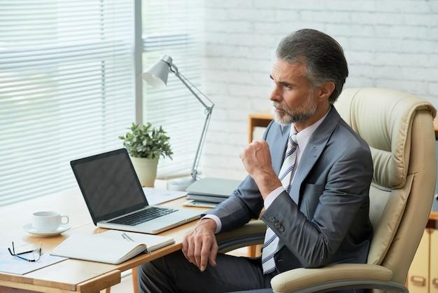 窓を思慮深く見てオフィスのテーブルでエレガントなビジネスマン