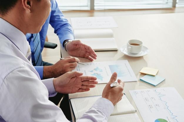 Обрезанные бизнесмены обсуждают аналитические визуальные эффекты и работают над бизнес-стратегией