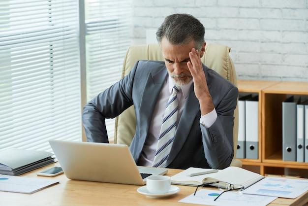 頭痛で彼の頭に触れるコンピューターデータに集中している実業家