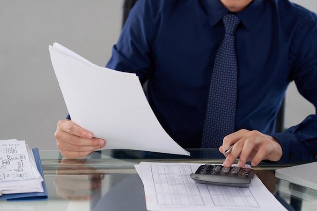 財務データを計算する匿名の男性会計士の中央部