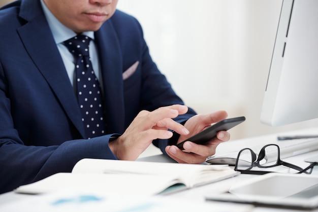 彼の眼鏡とデスクトップ上のノートブックで机に座っている彼の電話でトリミングされた実業家テキストメッセージ